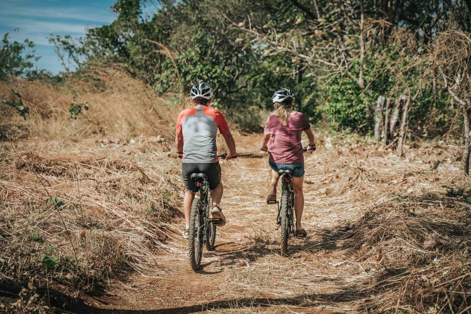 Bicycle riders biking down a path in Costa Rica on free bicycles from Drift Away Eco-Lodge.