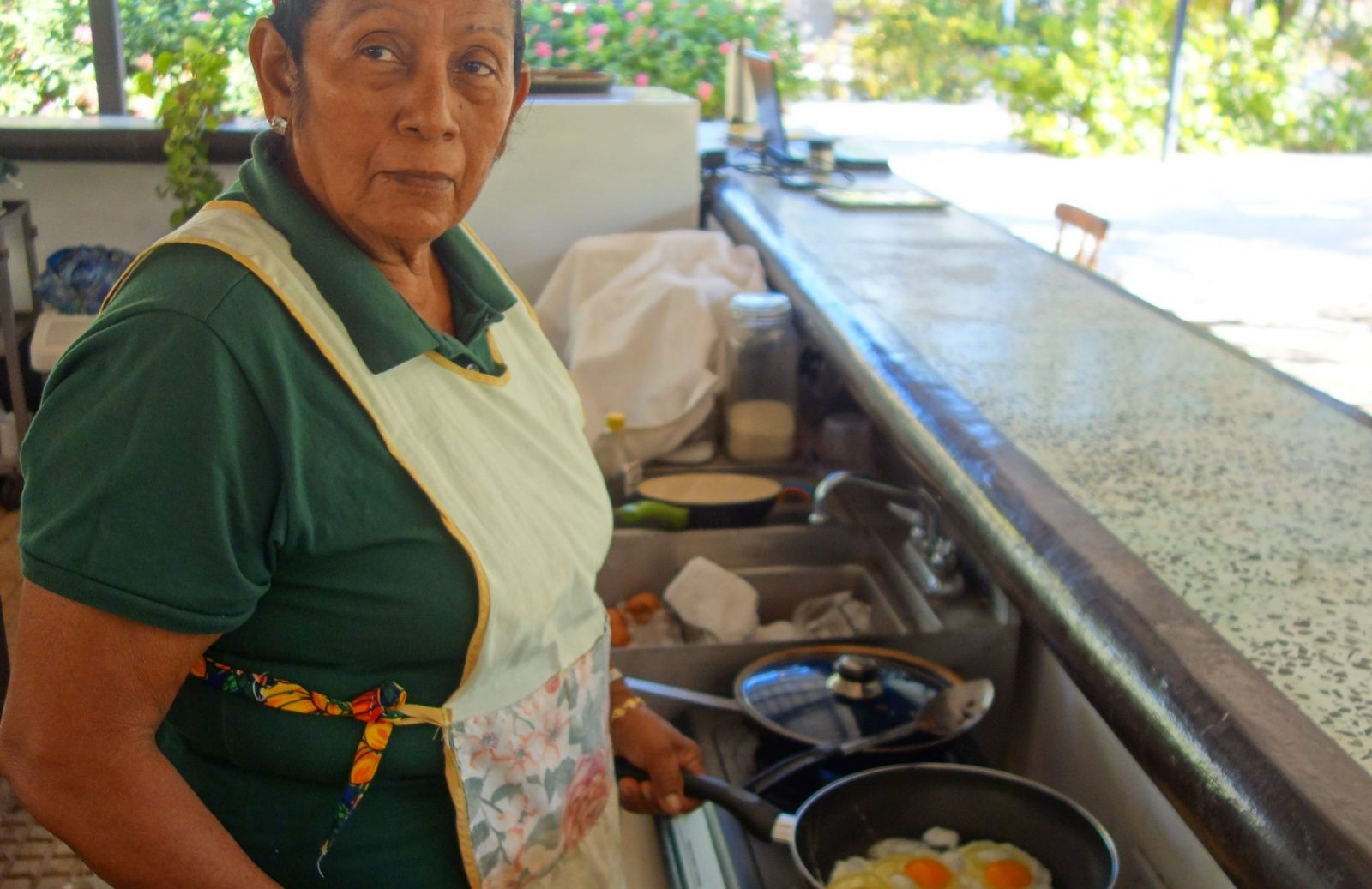 Rosa cooking eggs for breakfast in the kitchen at Drift Away Eco-Lodge.