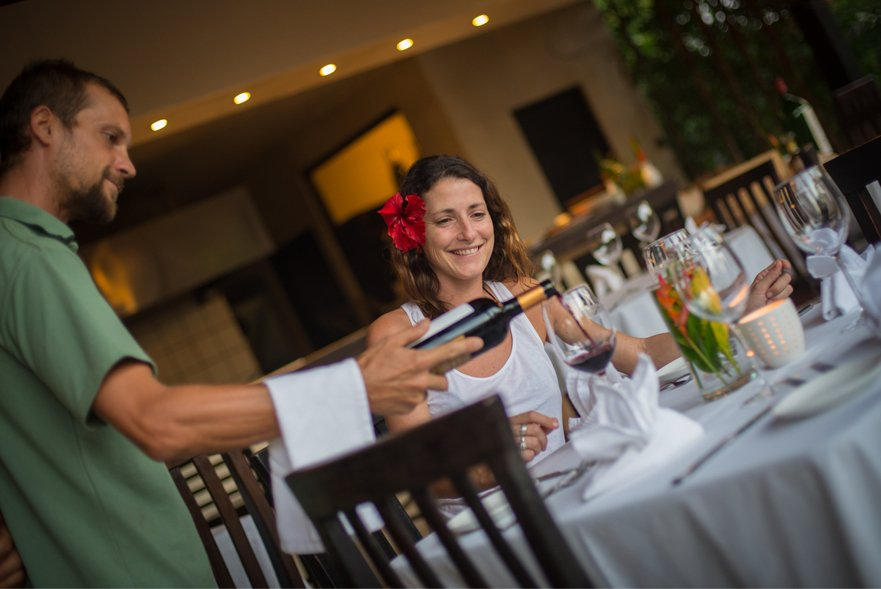 waiter pouring red wine for guest sitting at restaurant table with white linen